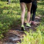 Kaksi juoksijaa juoksemassa metsäpolulla