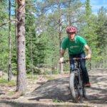 Mies pyöräilee metsässä fabikella.