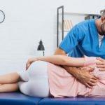 Fysioterapeutti tunnustelee pöydällä makaavan asiakkaan selkää ja olkapäätä.